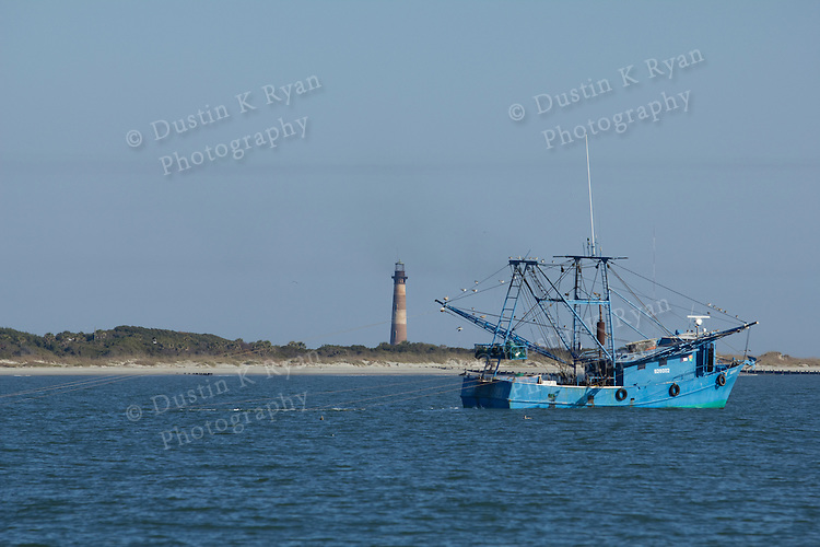Shrimp boat off folly beach on the Atlantic Ocean South Carolina Blue Morris Island Lighthouse