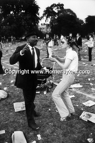 Rock Against Racism March and Concert. March from Hyde Park to Brockwell Park near Brixton London 1978. Mixed race couple dancing in Brockwell Park their baby in pram.