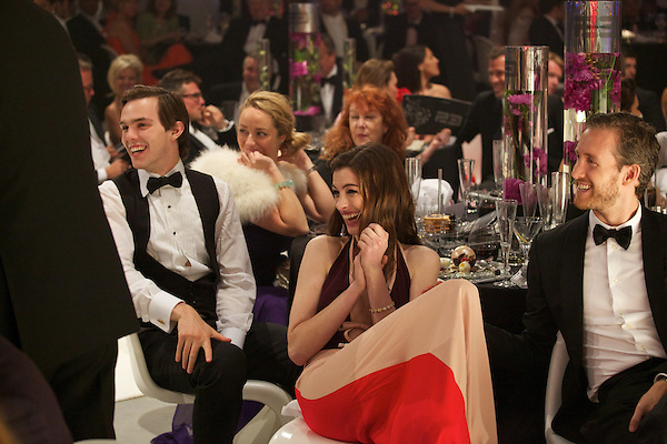 Nick Hoult and Anne Hathaway laugh at speeches during Elton John's White Tie and Tiara Ball