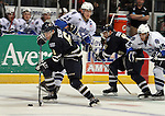 SIOUX FALLS, SD - APRIL 16:  Kyle Schempp #6 from the Sioux Falls Stampede pushes the puck past Mike McKee #23 from the Lincoln Stars in the first period of their 2013 USHL playoff game Tuesday night at the Sioux Falls Arena. (Photo by Dave Eggen/Inertia)