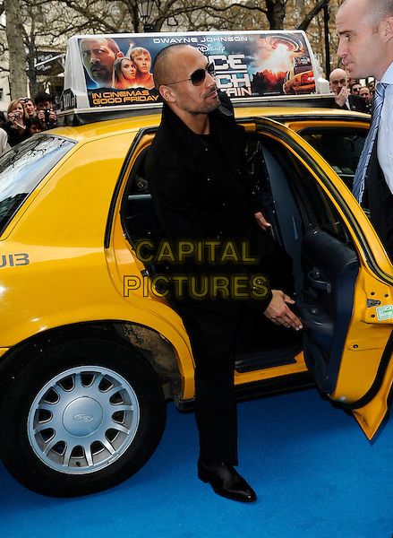"DWAYNE ""THE ROCK"" JOHNSON.The UK film premiere of ""Race To Witch Mountain"" at Odeon Cinema West End, London, England..April 5th 2009.full length black jacket trousers sunglasses shades yellow cab car taxi.CAP/CAN.©Can Nguyen/Capital Pictures."