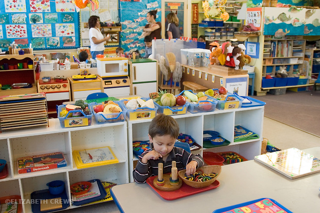 "Berkeley CA  Boy  doing solitary play in busy preschool classroom, showing various centers, art, ""house"", puzzles."