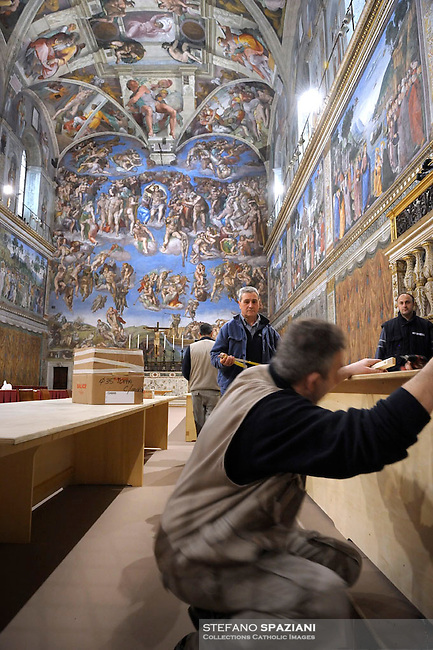 inside the Sistine Chapel ahead of cardinals in conclave, workers work in preparation for the conclave of 12 March 2013. Vatican Palace on March 9, 2013