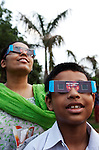 Saraswati De with her son Ananyapm (8) lines up to watch the longest solar eclipse this century through a specially erected screen. The eclipse drew big crowds to New Delhi's Nehru Planatarium to see the spectacular views of the moon passing the face of the sun. The eclipse was seen across India before focus shifted towards China and Japan. Many people stayed indoors for supersticious reasons whilst others celebrated with prayer and ceremony.