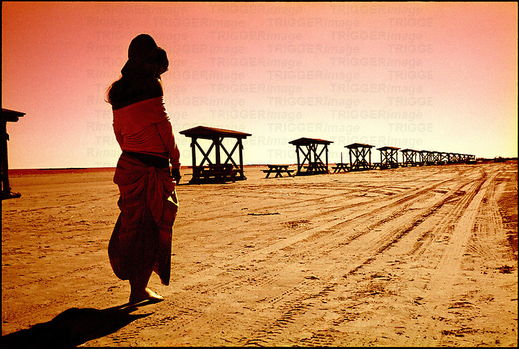 A woman facing away from the camera standing on a sandy beach
