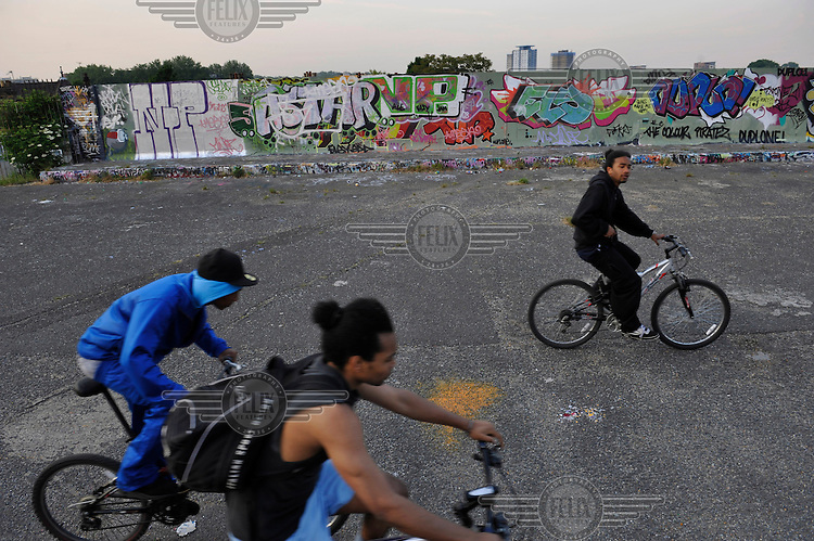 Youths cycle past a section of wall covered in graffiti  along the Green Way, between West Ham and Plaistow, London. ..