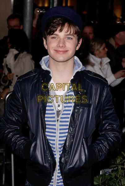 "CHRIS COLFER .""The Tempest"" Los Angeles Premiere held at the El Capitan Theatre, Hollywood, California, USA..December 6th, 2010.half length navy black shiny jacket white striped stripes top hands in pockets leather.CAP/ADM/CH.©Charles Harris/AdMedia/Capital Pictures"