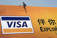 Chinese workers install a huge billboard of Visa Card in Beijing, China..