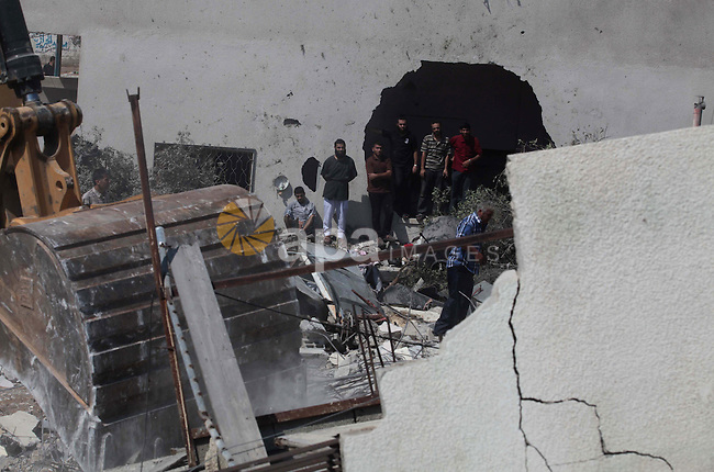 Palestinian rescue workers search for survivors under the rubble of a house was destroyed by an Israeli missile strike, in Gaza City, Monday, July 21, 2014. On Sunday, the first major ground battle in two weeks of Israel-Hamas fighting exacted a steep price, killing scores of Palestinians and over a dozen Israeli soldiers and forcing thousands of terrified Palestinian civilians to flee their devastated Shijaiyah neighborhood, which Israel says is a major source for rocket fire against its civilians. Photo by Ashraf Amra