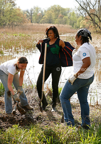 Washington, DC - April 21, 2009 -- Michelle Obama sheds her jacket during a tree planting event at the Kenilworth Aquatic Gardens in Washington, DC, April 21, 2009. The event was organized by the Student Conservation Association, an Americorp organization. .Credit: Martin H. Simon - Pool via CNP
