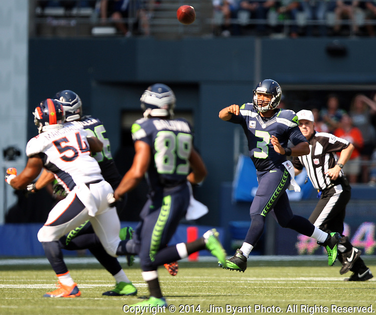 Seattle Seahawks quarterback Russell Wilson (3) passes against the Denver Broncos at CenturyLink Field in Seattle, Washington on September 21, 2014.  Wilson completed 24 of 34 passes for 258 yards, two touchdowns and one interception in the 26-20 overtime win against the Broncos.  ©2014. Jim Bryant Photo. All rights Reserved.