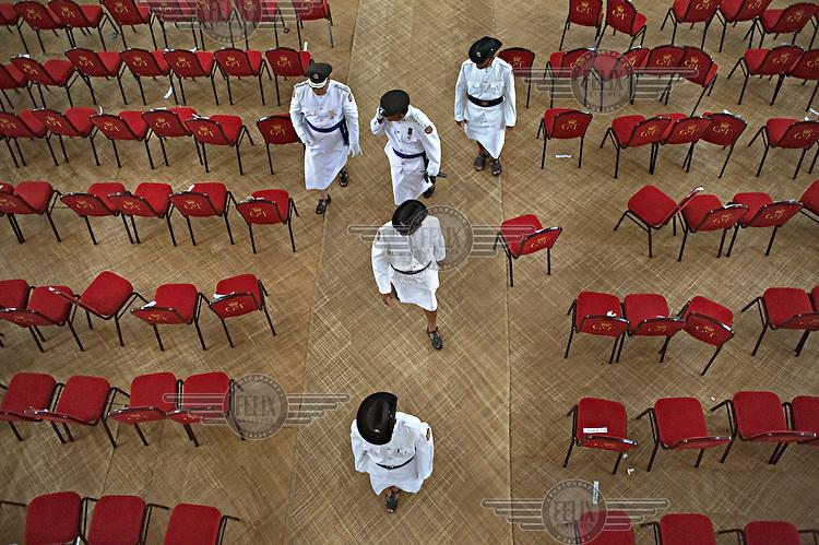 Men in Tongan military dress walk through the church following the coronation of King George Tupou V.