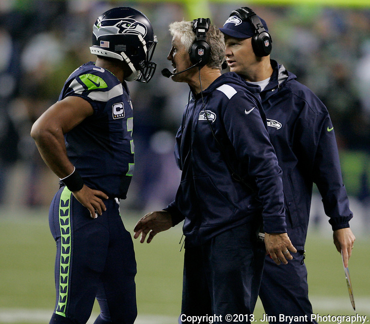 Seattle Seahawks head coach Pete Carroll, center,  talks quarterback Russell Wilson during their game against the San Francisco 49ers in the fourth quarter at CenturyLink Field in Seattle, Washington on September 15, 2013.  What a better way for the Seahawks' San Francisco-born coach to celebrate his 62nd birthday than to roam the sideline at CenturyLink Field during his team's 29-3 win over their NFC West rival 49ers.     ©2013. Jim Bryant Photo. ALL RIGHTS RESERVED.