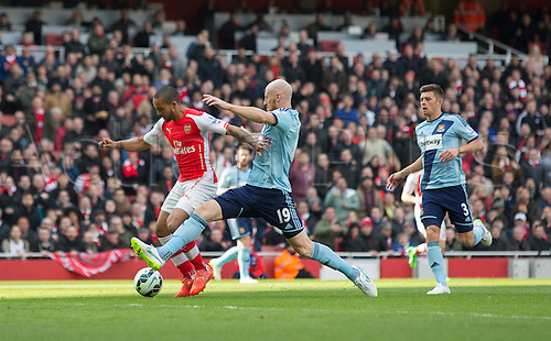 14.03.2015.  London, England. Barclays Premier League. Arsenal versus West Ham. West Ham United's James Collins challenges Arsenal's Theo Walcott.