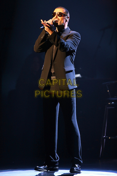 George Michael.premieres his European Orchestral Tour 'Symphonica' at the Prague State Opera House, Czech Republic  22nd August 2011..performing concert gig live on stage singing black suit sunglasses full length shades singing hand arm .*Editorial Use Only*.CAP/PLF.Supplied by Capital Pictures.