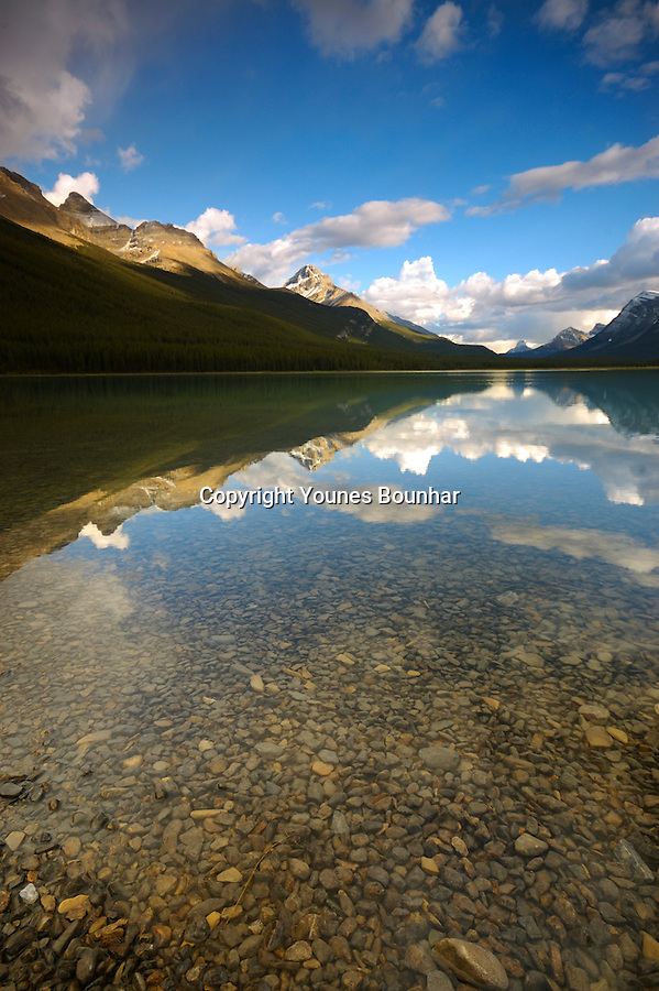 Moving clouds over waterfowl lake reflection in the late afternoon light