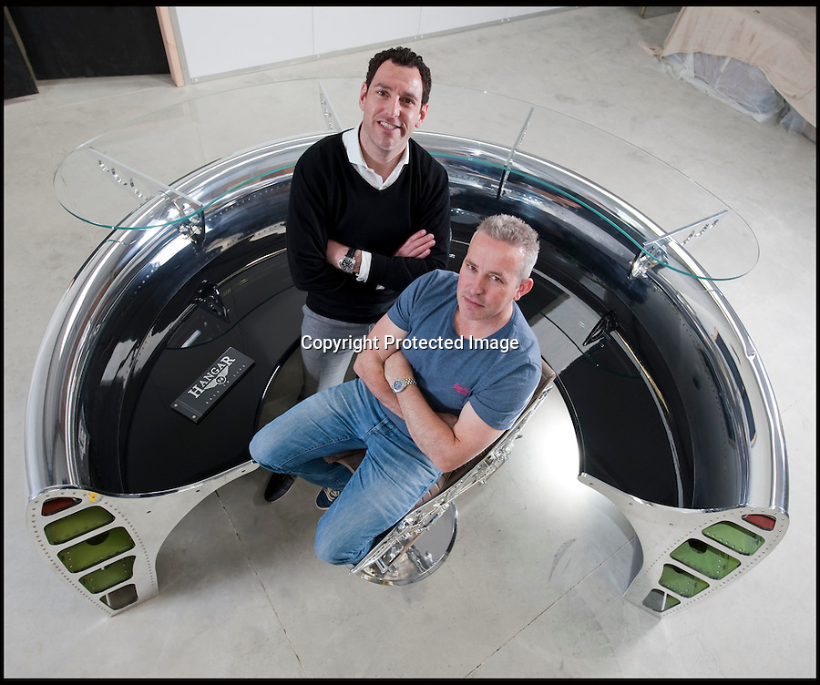 BNPS.co.uk (01202 558833)<br /> Pic: PhilYeomans/BNPS<br /> <br /> Bespoke furniture for the Jet Set.<br /> <br /> Brett and Shane Armstrong at a £20,000 reception desk made from a 737 engine intake.<br /> <br /> Two brother's have come up with ultimate in aircraft recycling - turning unwanted bits of redundant airliners into highly desirable - and highly expensive - bespoke items of furniture.<br /> <br /> Brett and Shane Armstrong from Kent scour the worlds aircraft graveyards looking for interesting items they can rescue from sad decay and with a lot of imagination and elbow grease convert into one-off gleaming items of furniture costing thousands of pounds.
