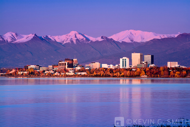 The Anchorage skyline at sunset as seen from the west at Earthquake Park, fall foliage, reflections of the buildings in the water, Fall , Anchorage, Alaska USA.