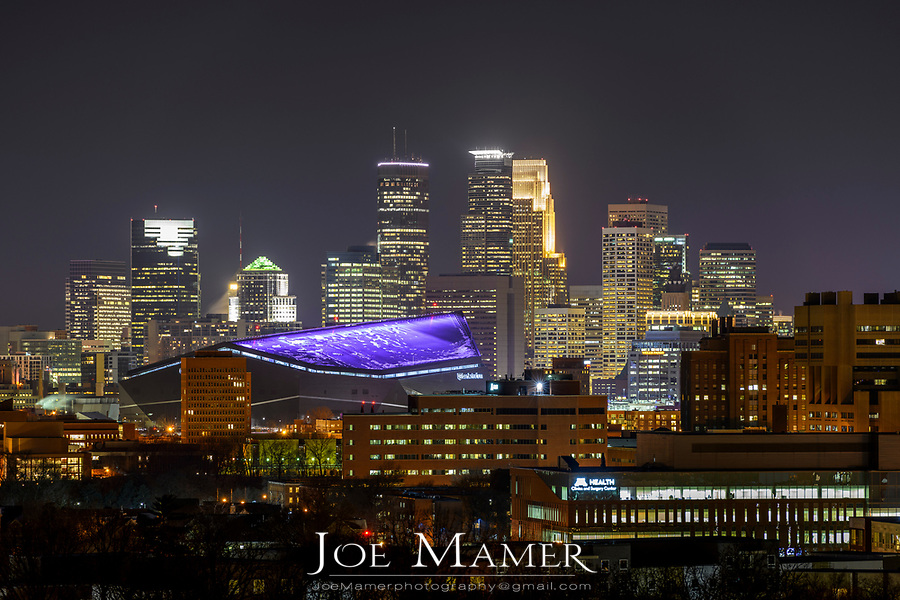 Minneapolis, Minnesota skyline with USBank stadium illuminated with a purple roof.