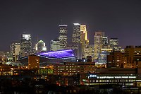 Minneapolis, Minnesota skyline with USBank stadium illuminated with a purple roof.