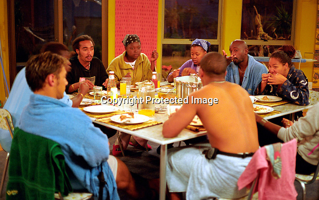 dipebig00011 Personalities. Big Brother Africa participants eating dinner in the house on July 20, 2003. From left  Stefan Ludik of Namibia, Mwisho Mwampamba from Tanzania, Cherise Makubale of Zambia, Warona Setshwaelo of Botswana,  Samuel Kwame Bampoe , Gaetano Kagwa of Uganda, Abby Plaatjes of South Africa and  Alex Holi of Kenya with his back to the camera. .©Per-Anders Pettersson/iAfrika Photos