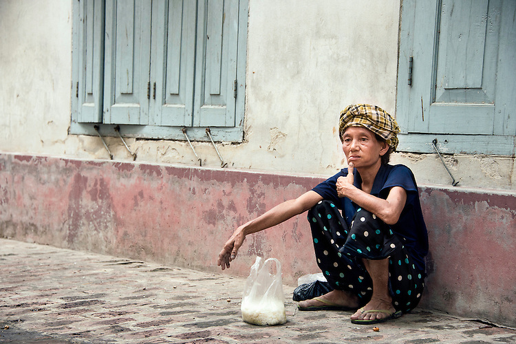 Burmese lady collects rice in Mandalay.