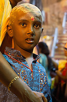 boy with shaved head and  body-painting, sacrifices to  to support salvation of ancestors among other rituals at Thaipusam ceremonies,  Batu Caves, Kuala Lumpur, Malaysia, 2012. Thaipusam ceremonies, celebrated by tamile Hindu community in Malaysia, take place  in Sanctuary of Batu Caves at the border of Kuala Lumpur, each year around end of January or beginning of February, according to Hindu moon calendar. The event is paying hommage to Lord Murugan, a spirit or god created by Shiva to lead the army of gods against the army of evil demons, finally defeating the evil spirits. There are many ways to present offerings or sacrifices for this major religious event. Devotees mortify their bodies by carrying heavy kavaris with spears fixed in their skin or fruits, flowers and little post with holy milk fixed with hooks in their skin, ascending the stairways to the sanctuary in trance, `followed by assistant  taking care and musicians playing loud and fast rhythmic trance music.  Many families shave their head in a ritual before ascending the stairways, as part of rituals to obtain salvation for their ancestors.