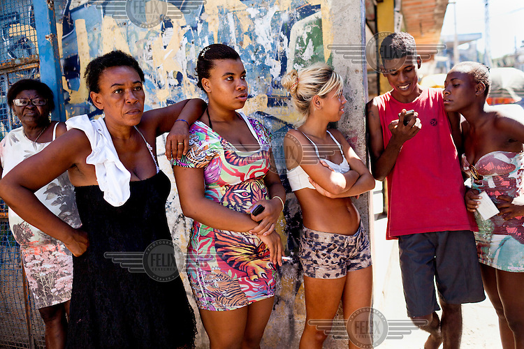 A group of residents in Favela do Metro watch as another set of evictions, of newer residents who are poorer and squatting in abandonned homes, take place near the Maracana Stadium.