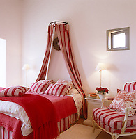 A feminine bedroom is decorated with red and white striped bed linen with bed hangings to match
