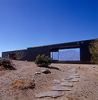 A path of slate stones winds its way through the dry desert landscape to the modern prefabricated structure of the house