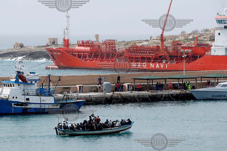 A small boat carrying illegal immigrants arrives at the port. Since the beginning of revolutions in their countries, hundreds of Libyan and Tunisian people a day cross from the northern coast of Africa to Lampedusa. About 90% of them are Tunisian.