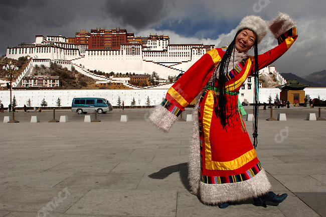 A Chinese tourist, whom had dressed in traditional Tibetan costume from a photographer's props, posed in front of the Potala Palace in Lhasa, the Tibetan capital. November 20, 2006
