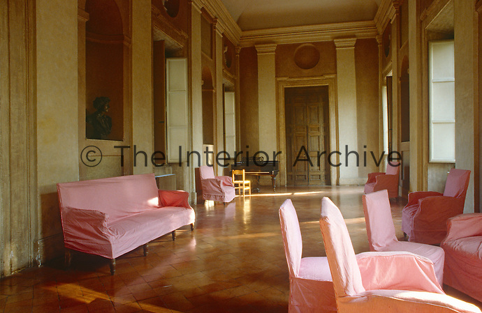 In a salon of the Villa Medici contemporary loose covers in rose-pink create a stunning contrast to the pale grey fresco of the walls