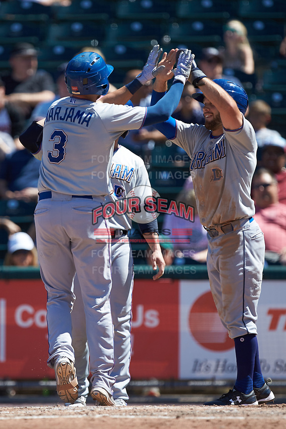 Mike Marjama (3) of the Durham Bulls high fives teammate Johnny Field (13) as he crosses home plate following his three-run home run against the Lehigh Valley Iron Pigs at Coca-Cola Park on July 30, 2017 in Allentown, Pennsylvania.  The Bulls defeated the IronPigs 8-2.  (Brian Westerholt/Four Seam Images)