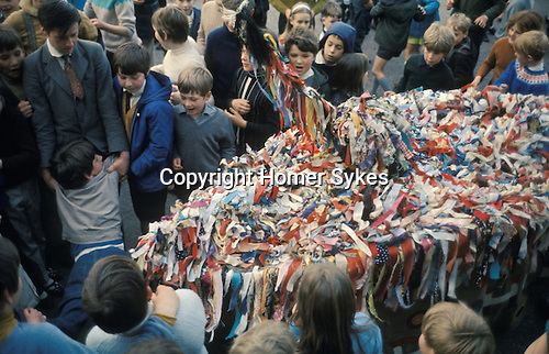 "Minehead Hobby Horse Somerset. UK.  ""Booting"" ceremony at Cher on last evening. A boy, a  young person is held out infront of the Hobby Horse and struck 10 times by the bow of the Hobby Horse."