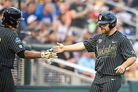 Vanderbilt Commodores outfielder Stephen Scott (19) is greeted by teammate Austin Martin (16) after scoring against the Michigan Wolverines during Game 2 of the NCAA College World Series Finals on June 25, 2019 at TD Ameritrade Park in Omaha, Nebraska. Vanderbilt defeated Michigan 4-1. (Andrew Woolley/Four Seam Images)
