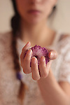 Photograph of a girl holding a purple flower in her hand