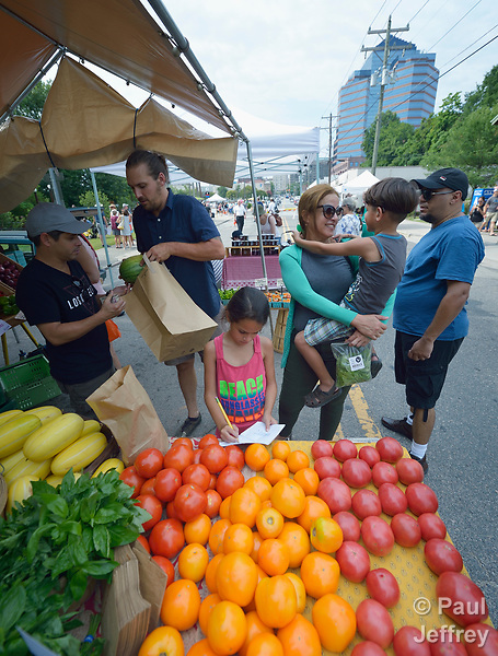 A Cuban refugee family shops in the Durham Farmers' Market in Durham, North Carolina. They were resettled in Durham by Church World Service, which resettles refugees in North Carolina and throughout the United States.<br /> <br /> Photo by Paul Jeffrey for Church World Service.