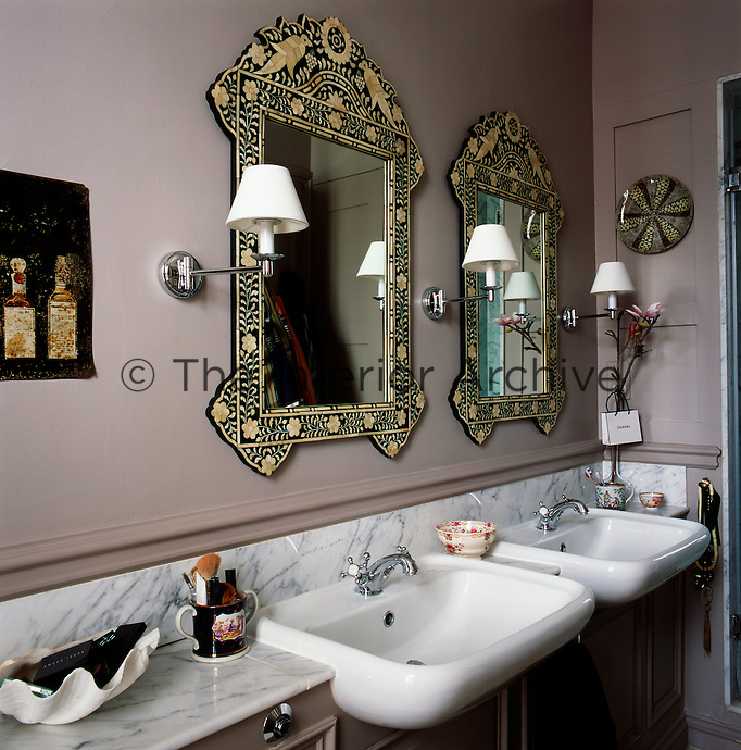 The bathroom has two ornately decorated mirrors above two washbasins, which are set on a cupboard unit. The marble top and surround adds a touch of luxury