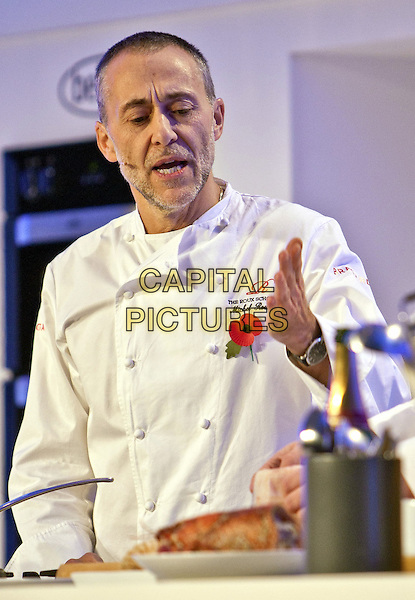 Michel Roux Jr.BBC Good Food Show London 2012, Olympia, Kensington, London, England..November 10th 2012.half length white chef jacket mouth open hand arm cook cooking poppy stubble beard facial hair  .CAP/MM/PP.©Mike Mustard/PP/Capital Pictures