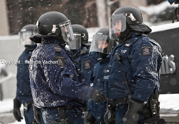 Two policemen in anti-riot gear chat during a protest in Quebec City Monday December 6, 2010.