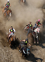 Riders and horses race down a steep slope during the Omak Stampede World Famous Suicide Race in Omak, Wash. on Sunday, August 15, 2015. (photo by Karen Ducey)