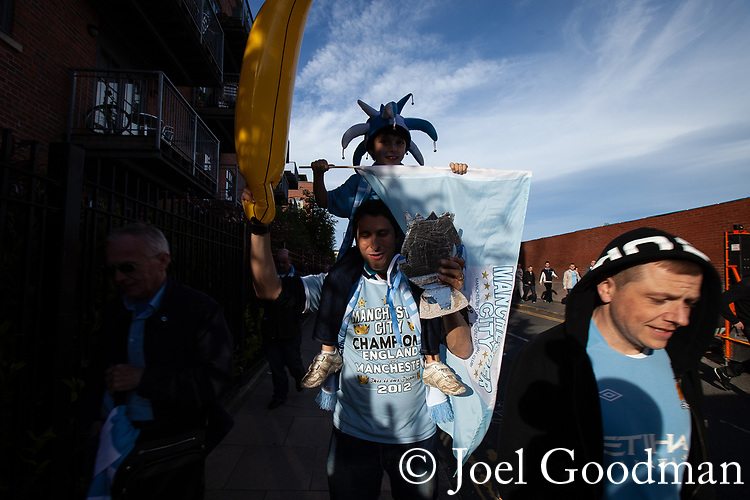© Joel Goodman - 07973 332324 . 13/05/2012 .  Manchester , UK . Manchester City Football Club fans celebrate outside the Etihad Stadium after the result of their match against QPR ensures Manchester City wins the Premiership title . Photo credit: Joel Goodman