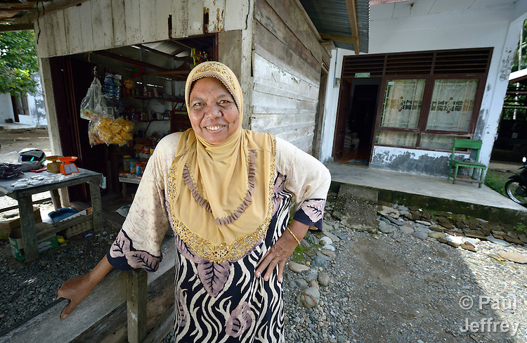 Nyak Minah stands in front of her home in Kubang Gajah in Indonesia's Aceh province. After the 2004 tsunami, the U.S.-based Catholic Relief Service built her a new home. She has added on to it, including a store on the front where she sells basic food items.