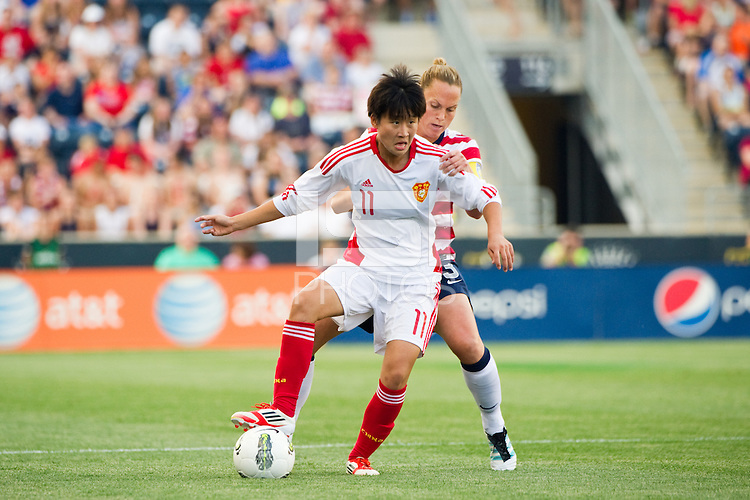 Lou Jiahui (11) of China PR (CHN) is marked by Christie Rampone (3) of the United States (USA). The United States (USA) women defeated China PR (CHN) 4-1 during an international friendly at PPL Park in Chester, PA, on May 27, 2012.