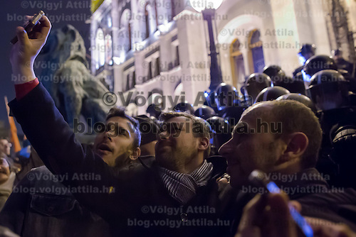 Protesters take a selfie in front of a line of riot police during a demonstration against government corruption in Budapest, Hungary on December 16, 2014. ATTILA VOLGYI