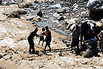 Travelers help each other across a makeshift bridge after a river washed out the road.