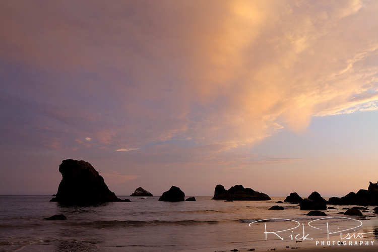 Light from the last of the day's light strike the clouds above the sea stacks at Rainbow Beach in Brookings, Oregon.