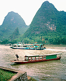 CHINA, Guilin, man traveling in boat on the Li River with Limestone mountains in the background