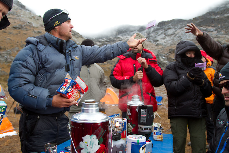 The 1st morning in basecamp involves sorting through piles of food.  Jeff Evans tossing out some breakfast bars. Photo by Didrik Johnck.